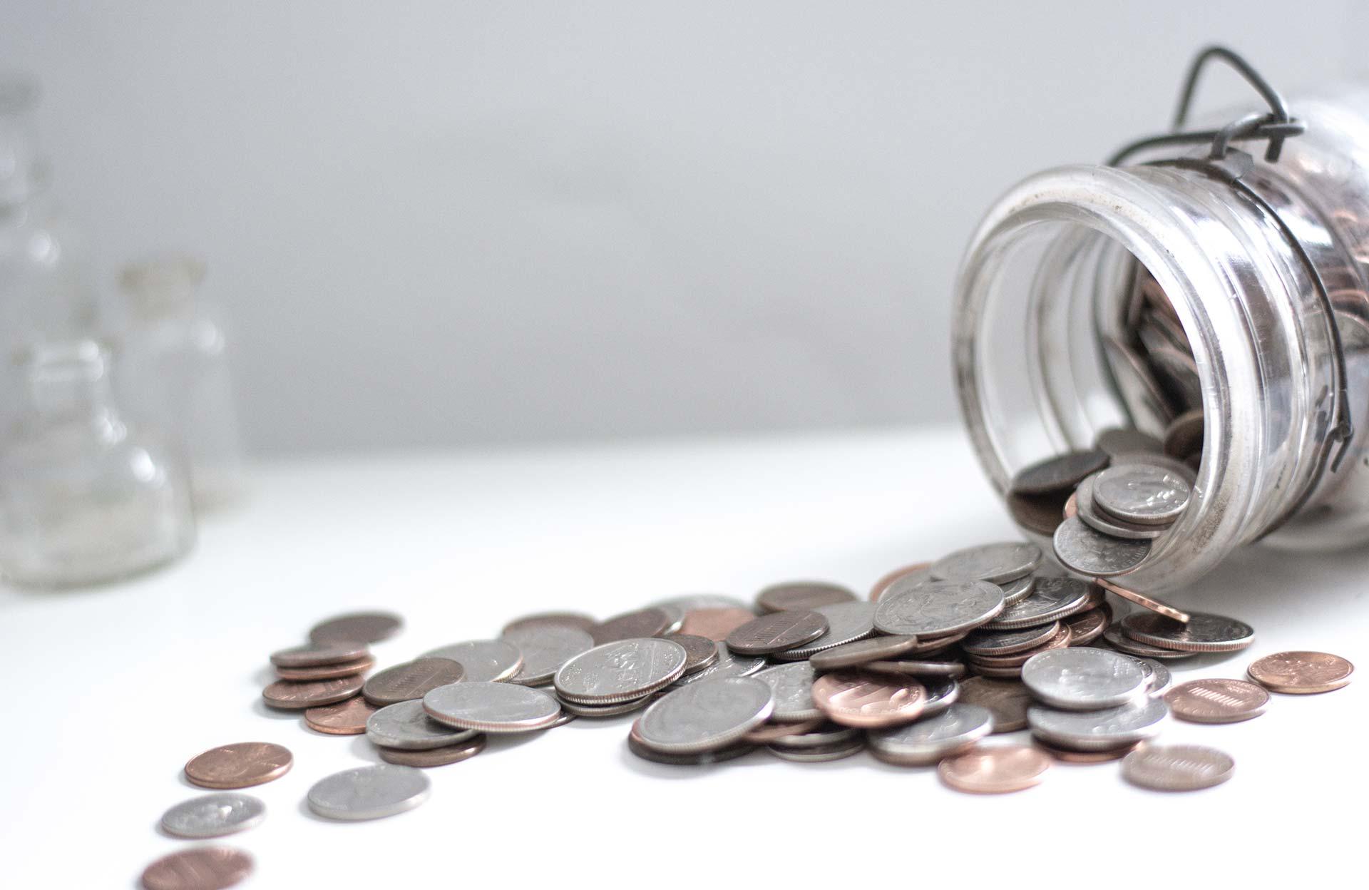Tarro de dinero derramando monedas en una mesa