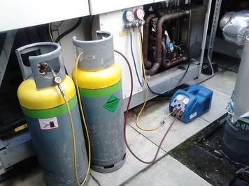 Carga de refrigerante con cilindros amarillos y verdes