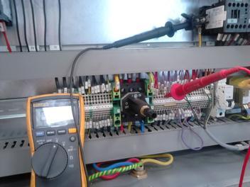 Multímetro digital en panel de control con sondas rojas y negras