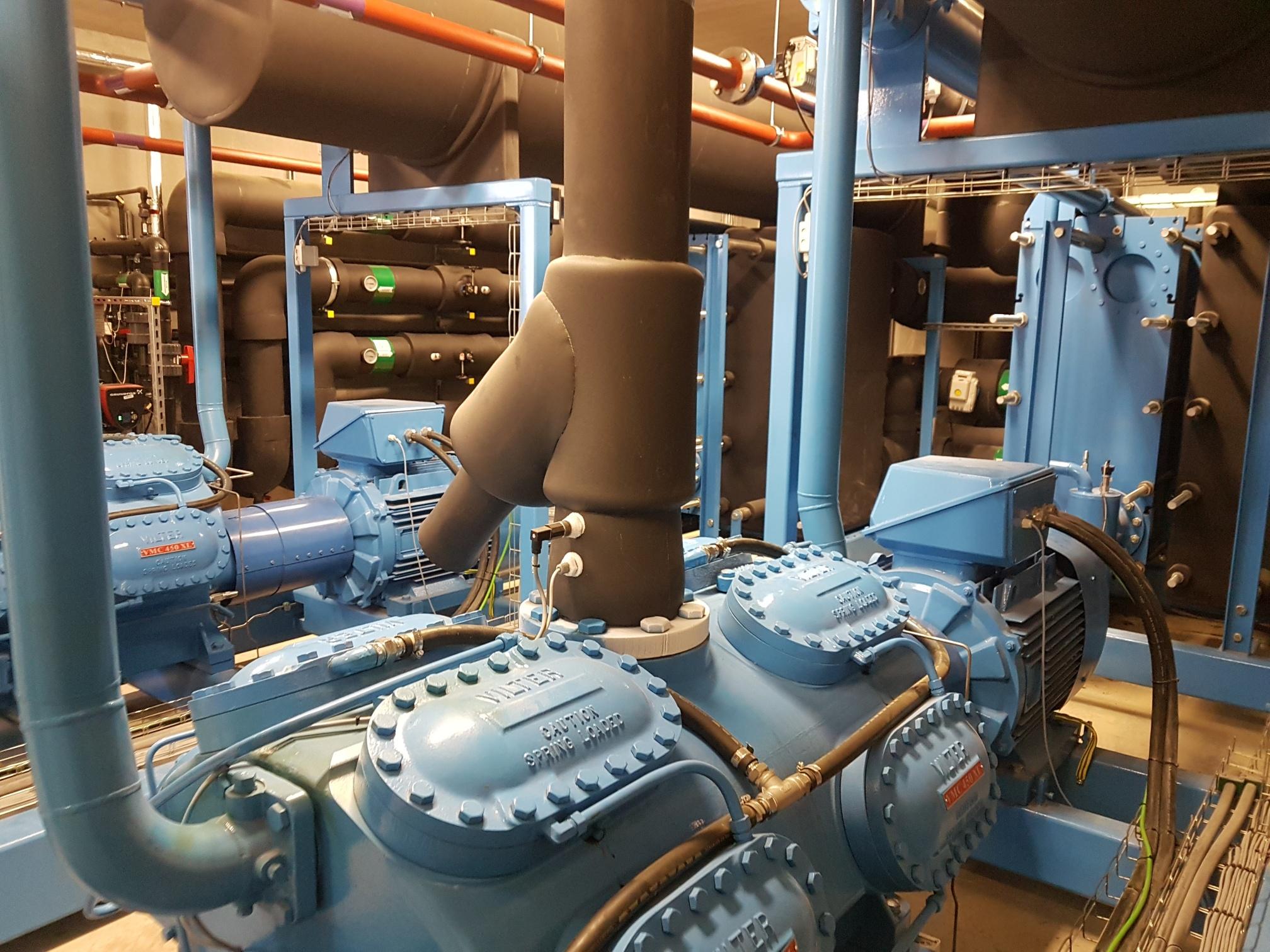 Sala de máquinas con enfriadoras de glicol azul y negro durante el servicio de mantenimiento y reparación
