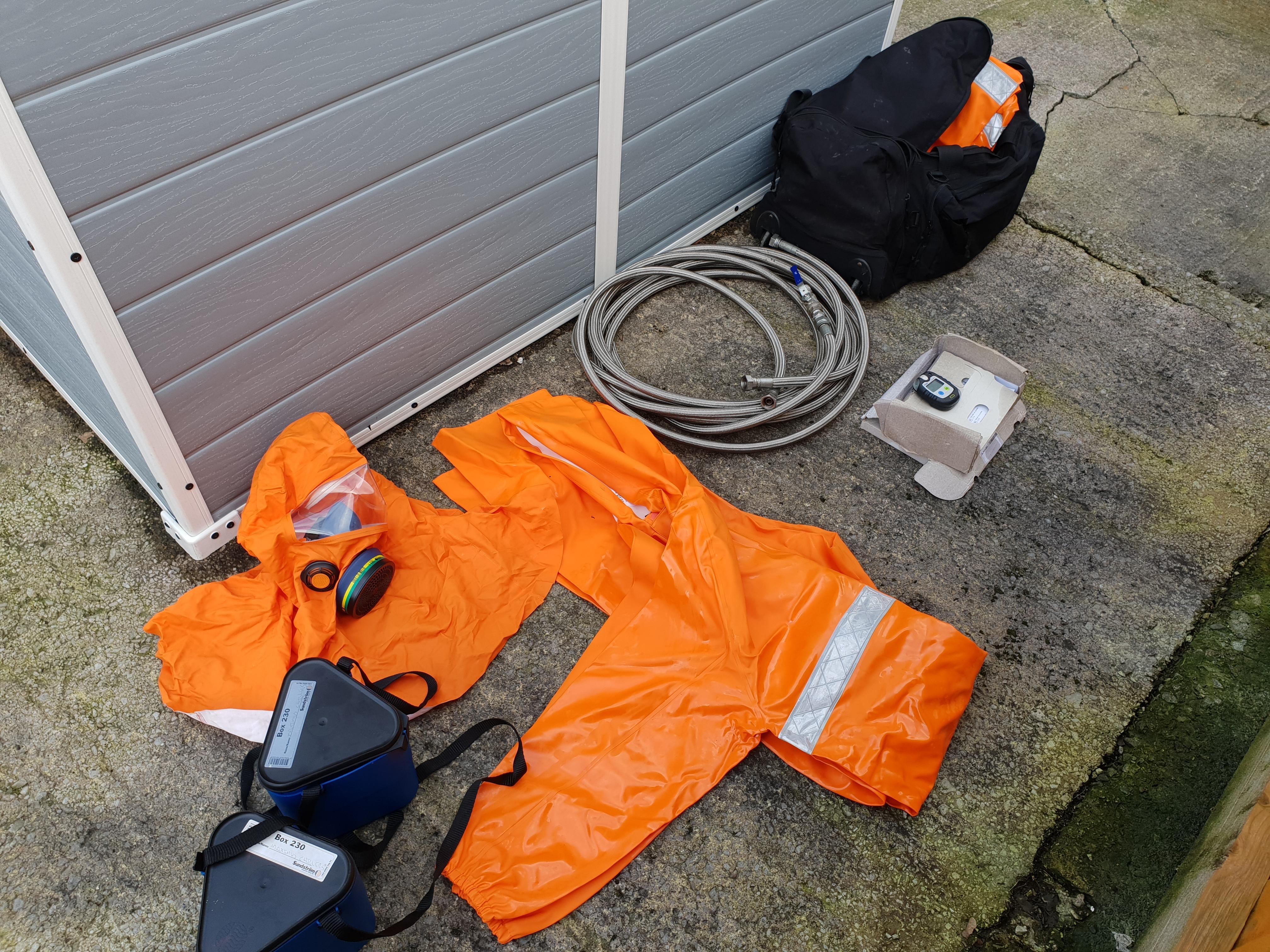 Traje químico naranja y manguera de carga para el mantenimiento, reparación y servicio de enfriadoras de amoníaco