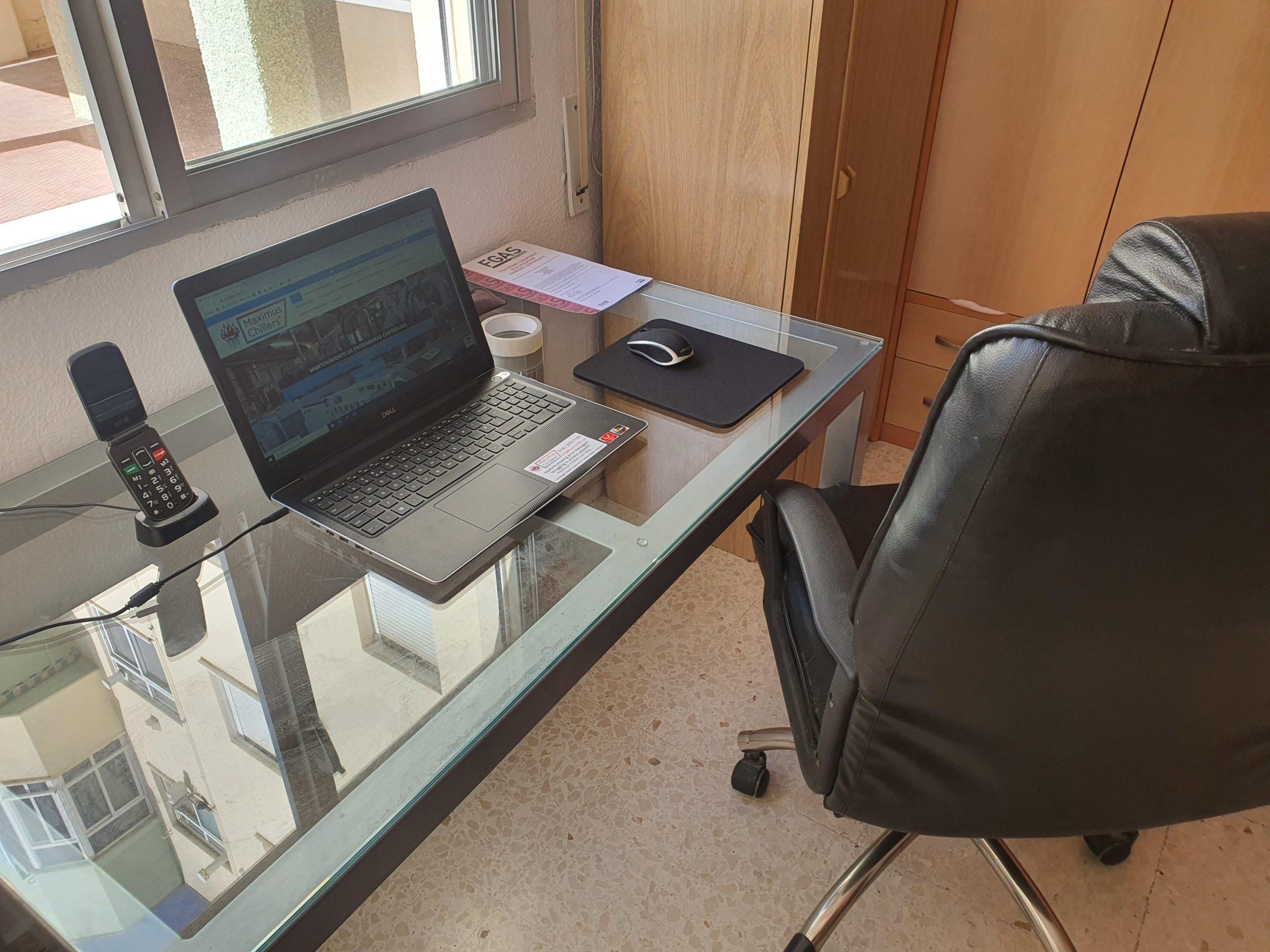 Un escritorio de cristal, portátil y silla ejecutiva en la oficina española