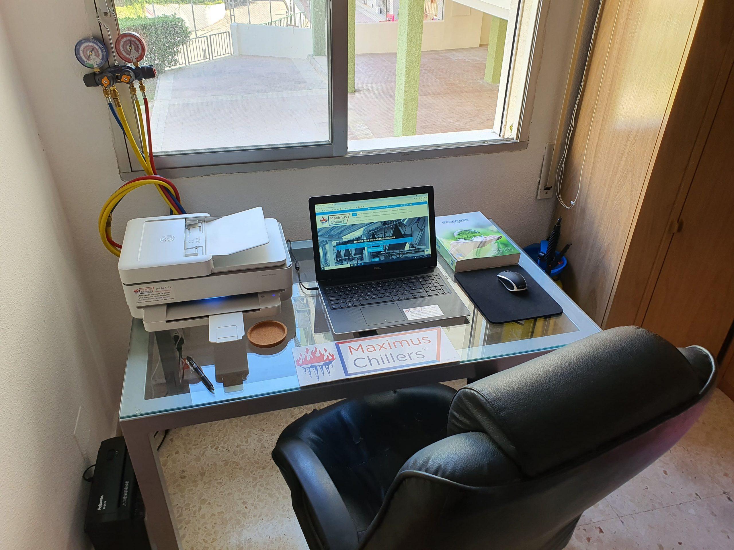Escritorio de oficina en España con ordenador, manómetros de refrigerante y impresora